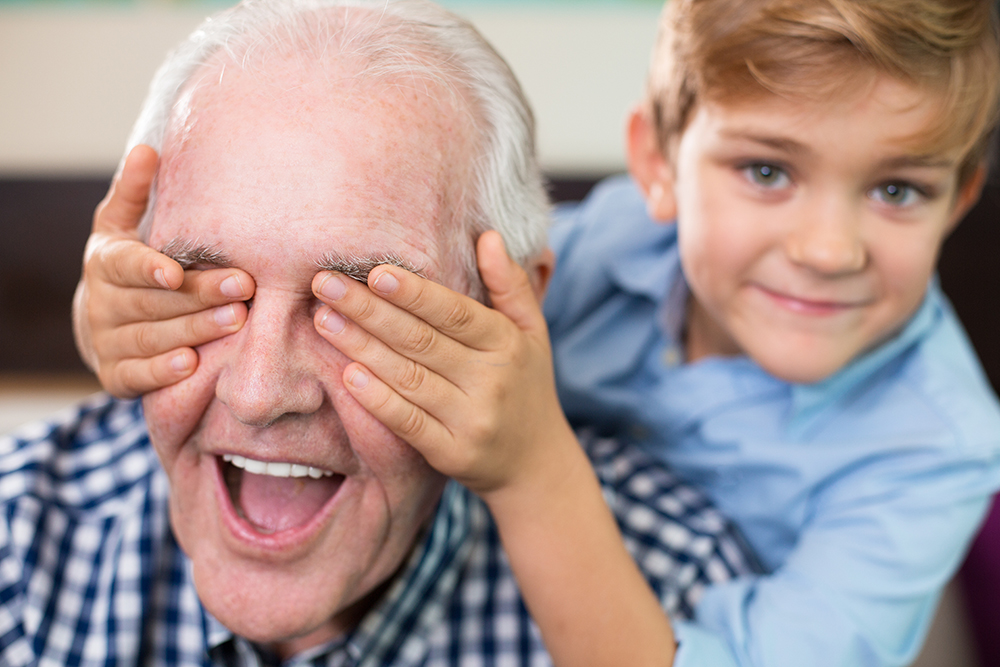 Close-up of face of happy senior man and little boy covering his eyes with hands. Grandfather at home with his grandson